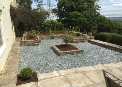 Raised flower beds with slate in a formal layout.